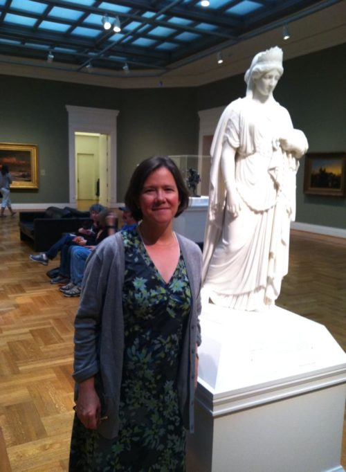 Photograph of Kate Culkin and a small model of Zenobia in Chains at the St. Louis Art Museum.